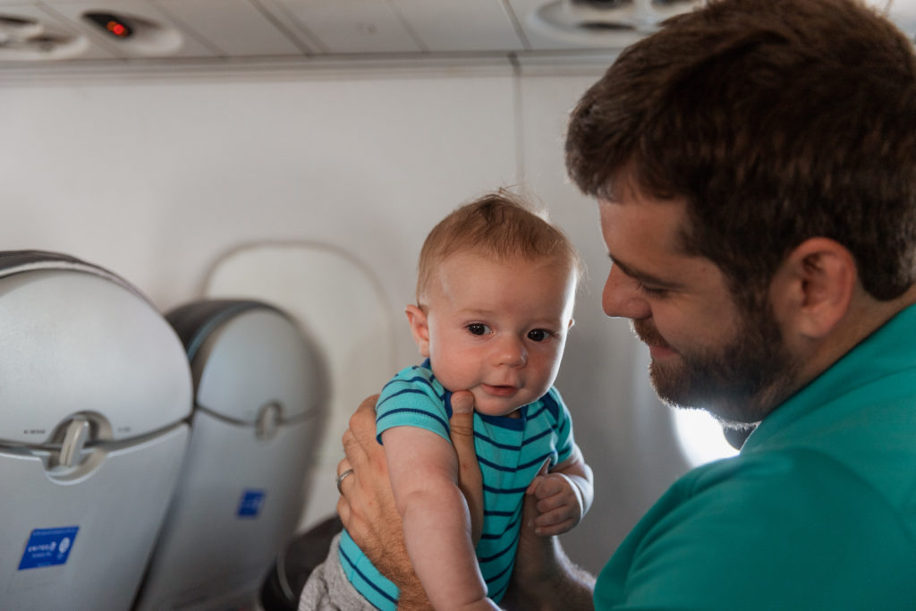 Babies also love the stimulus on the plane. Dad holding his baby on the plane.
