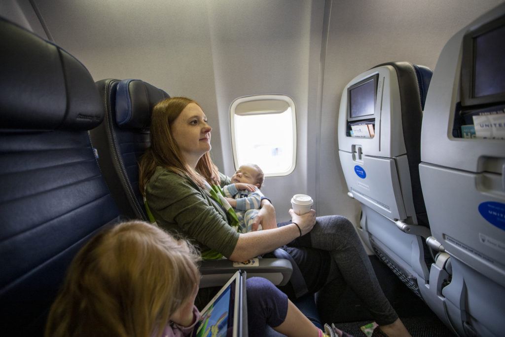 Babies really do sleep all the time. Mom and children sitting in an airplane.