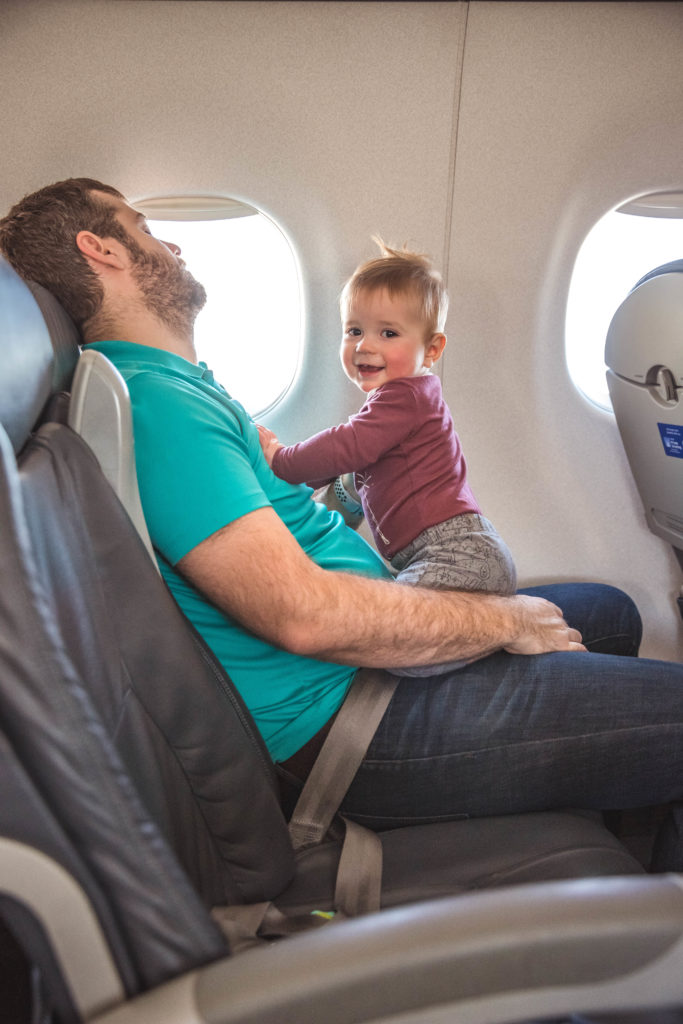 Happy baby sitting on sleeping dad on airplane