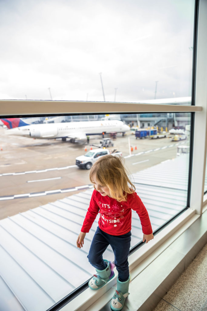 Toddler playing by a window at the airport