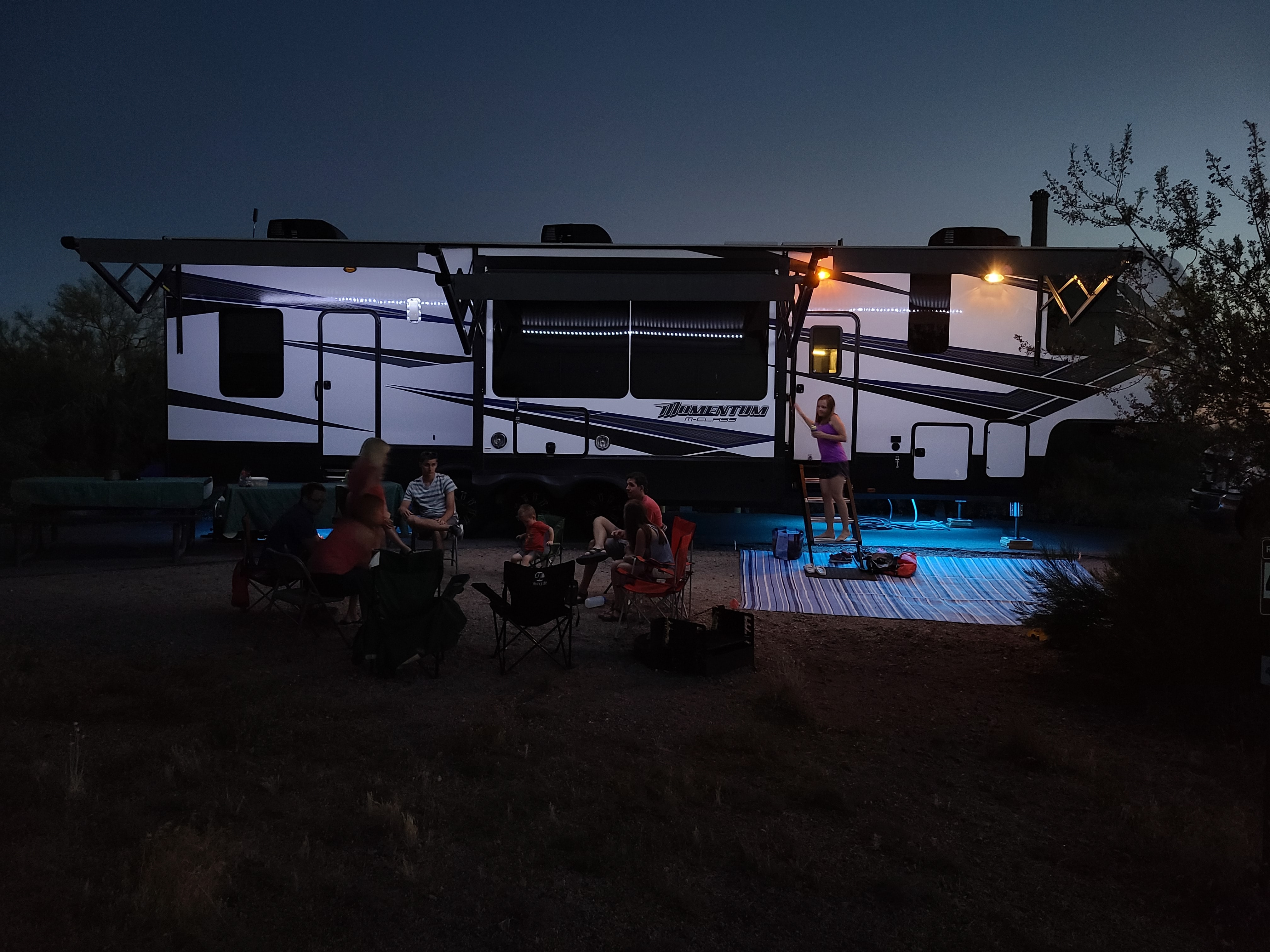 kids relaxing outside an RV during a family RV trip