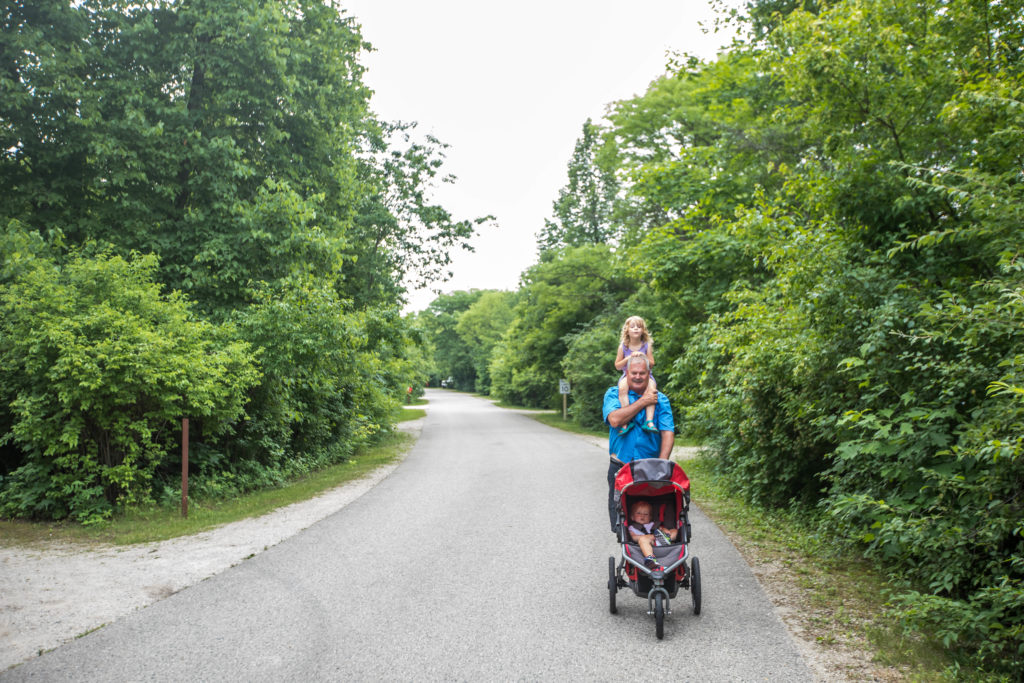 Grandpa takes one year old and four year old for a walk around campground in state park