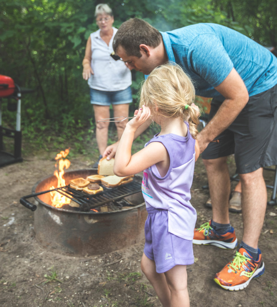4 year old helping dad cook burgers over campfire with tent camping