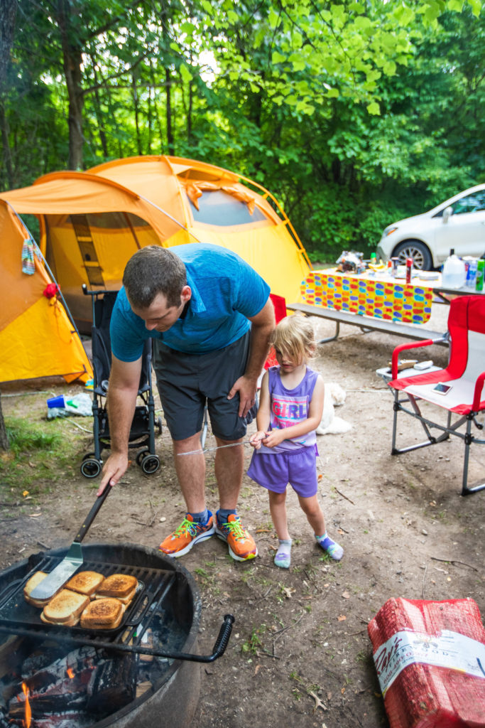 dad cooks lunch with 4 year old daughter over campfire | tent camping with toddlers