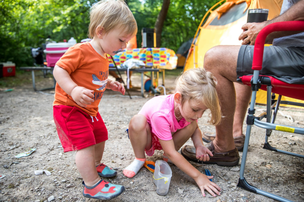 Toddlers playing in the dirt while tent camping for the first time