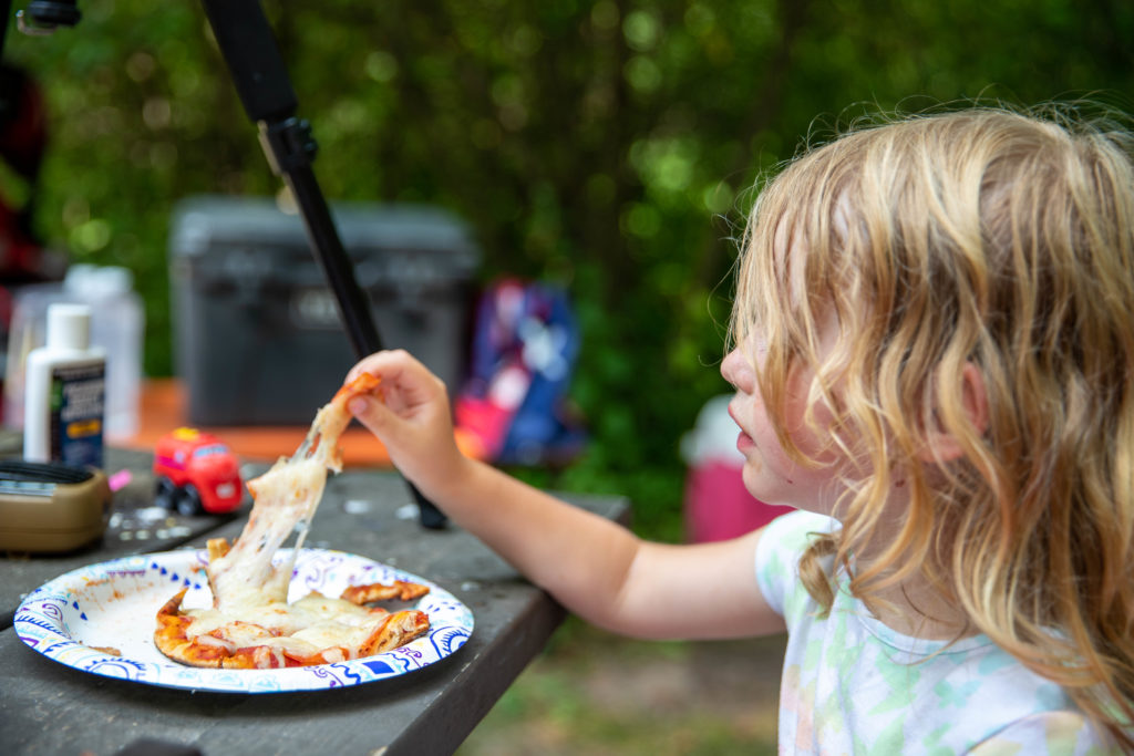 4 year old eating a pepperoni naan pizza cooked over campfire