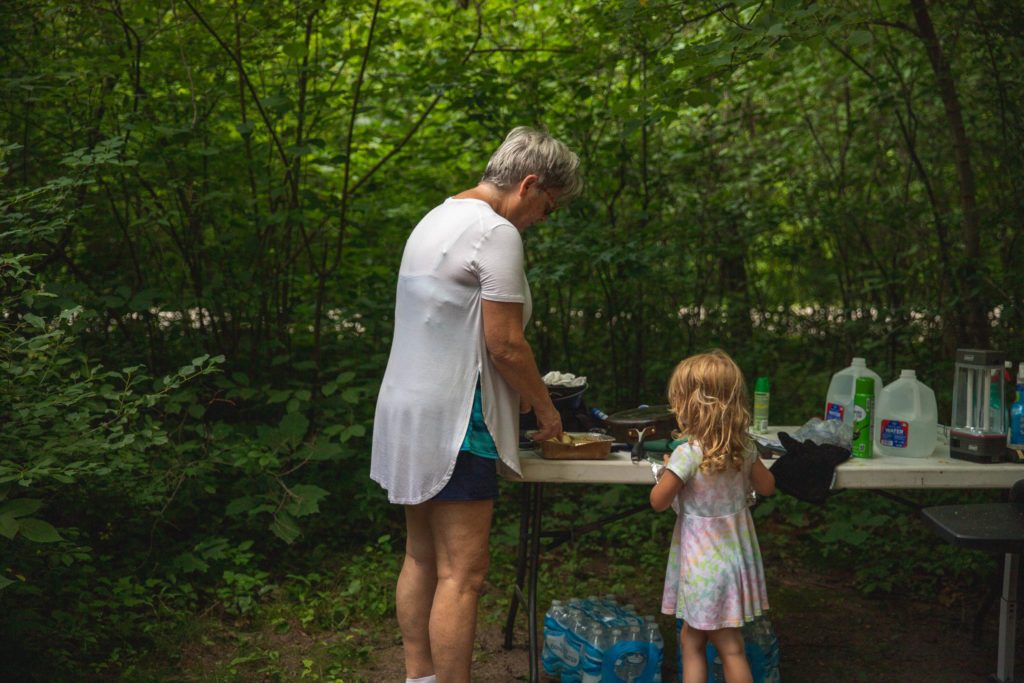 4 year old prepares lunch with grandma while tent camping
