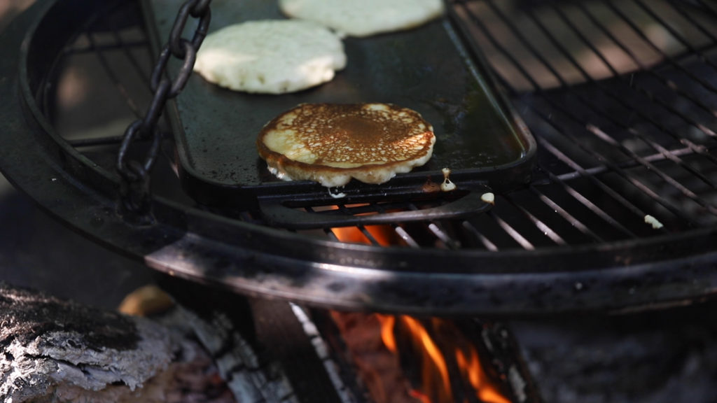 Pancakes cooking over a campfire griddle | camping meals for kids