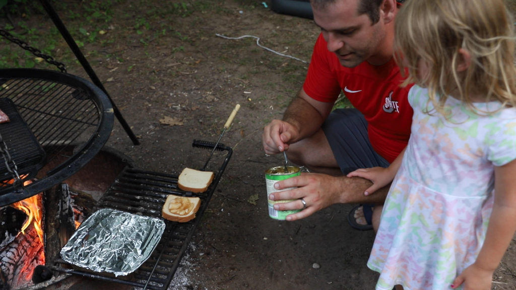 Dad and daughter cooking an apple camp pie together over the campfire