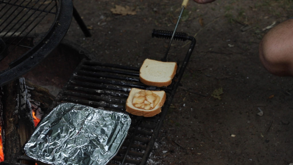 An apple filled camp pie being cooked over a fire while camping