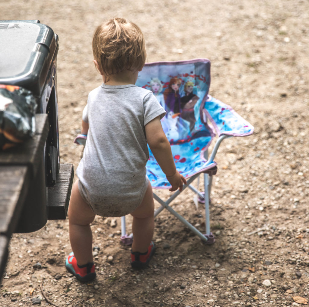 A one year old with a kids camping chair during a family camping trip