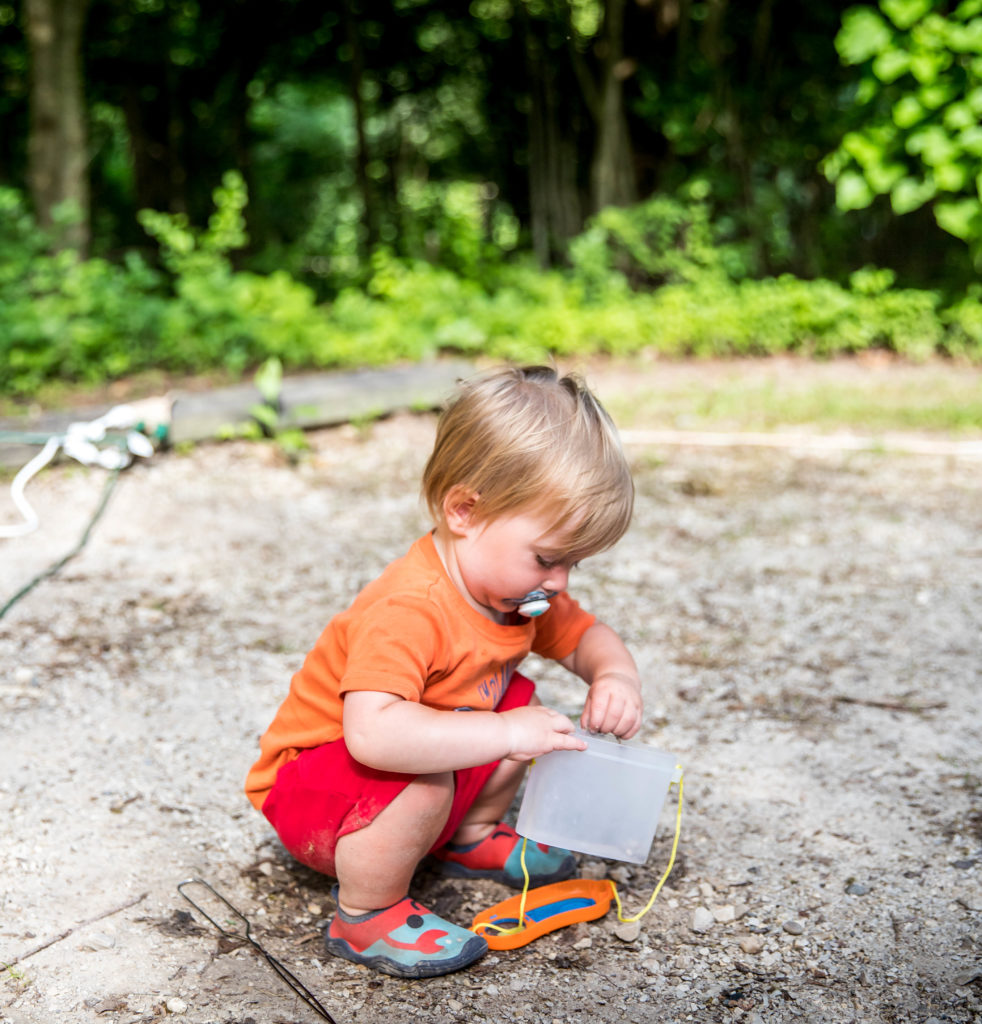 One year old playing with a bug catching kit | camping essentials for kids