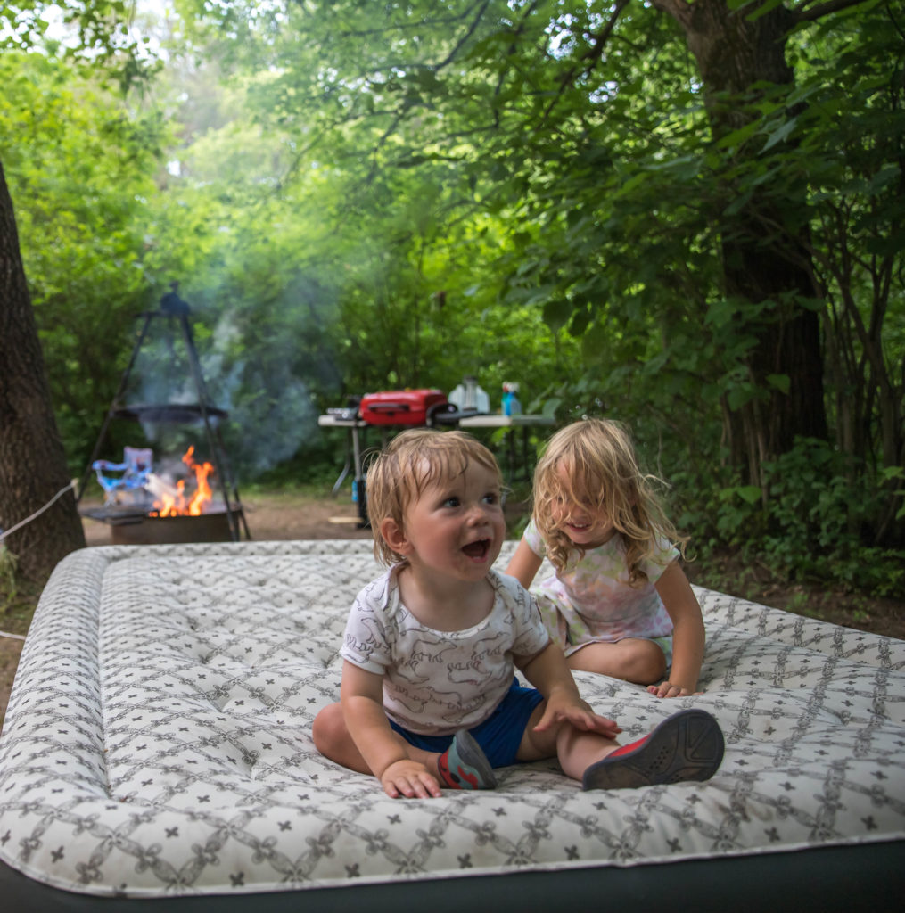 Two kids playing on an outdoor air mattress while camping with family