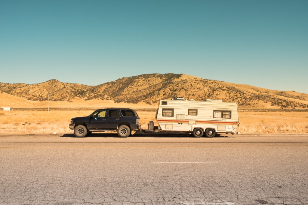 A car towing a travel trailer through the desert