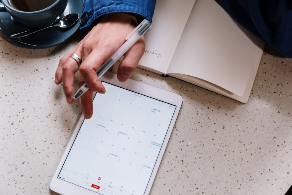 woman plans out her schedule on a tablet