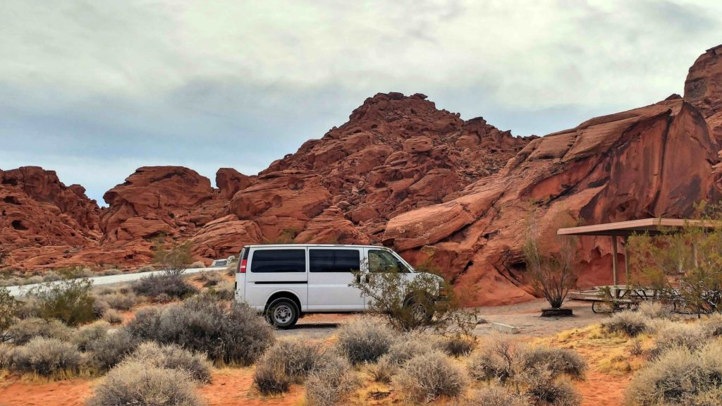 Camper van parked at campsite | how to plan a cross country road trip on a budget