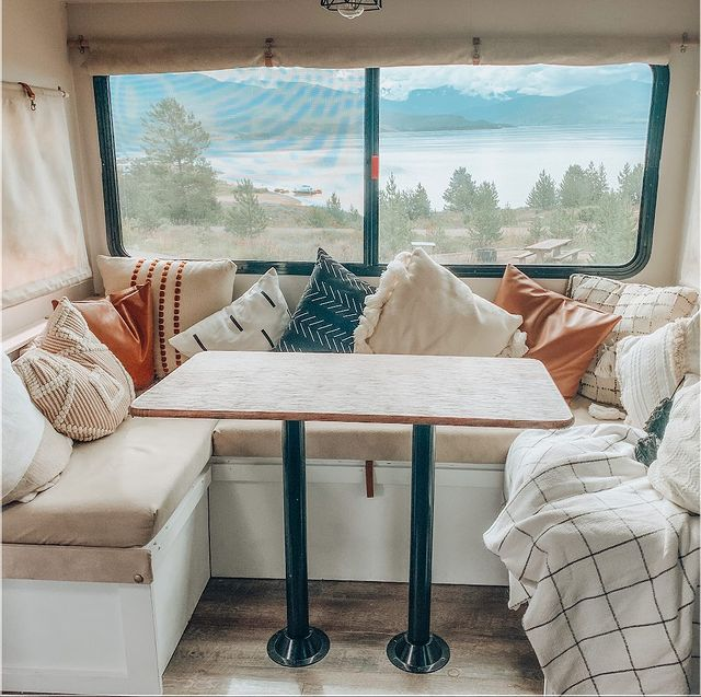 View outside a camper window from a cozy seating area
