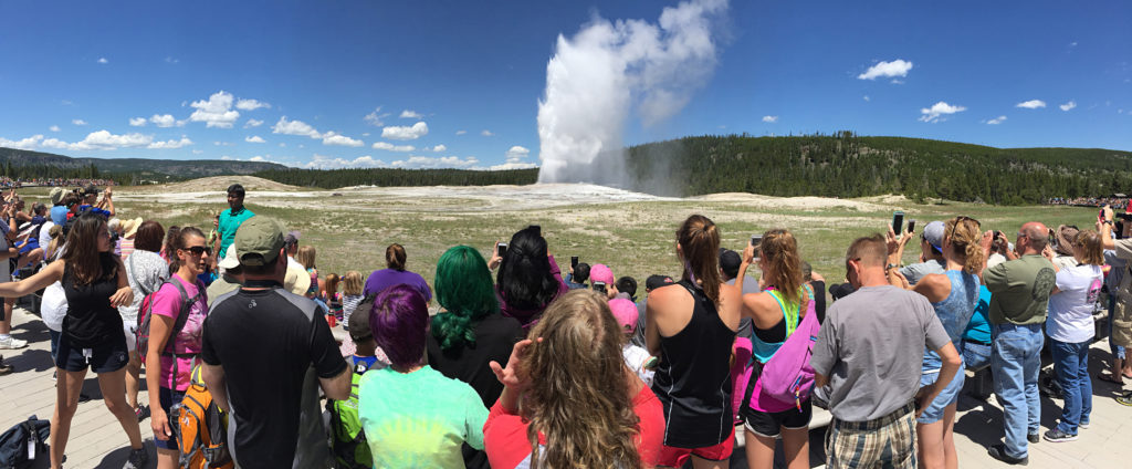 Crowds watching the Old Faithful Geyser from the nearby benches