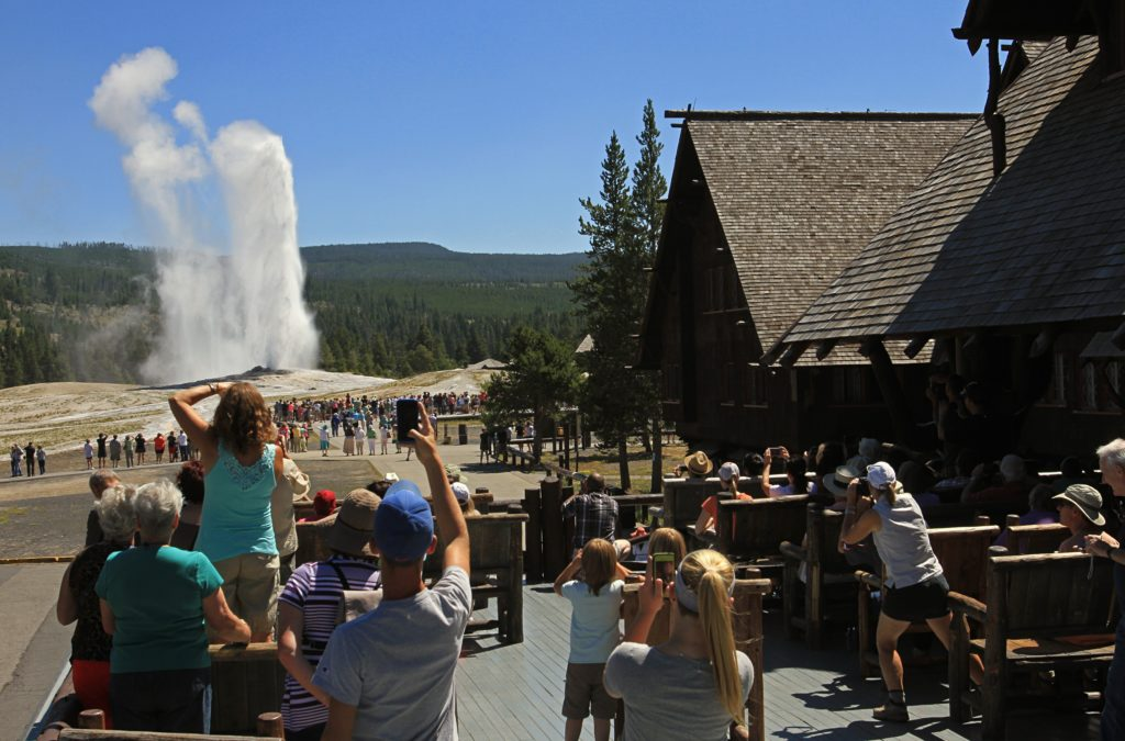 Visitors watching Old Faithful Geyser from the Old Faithful Inn