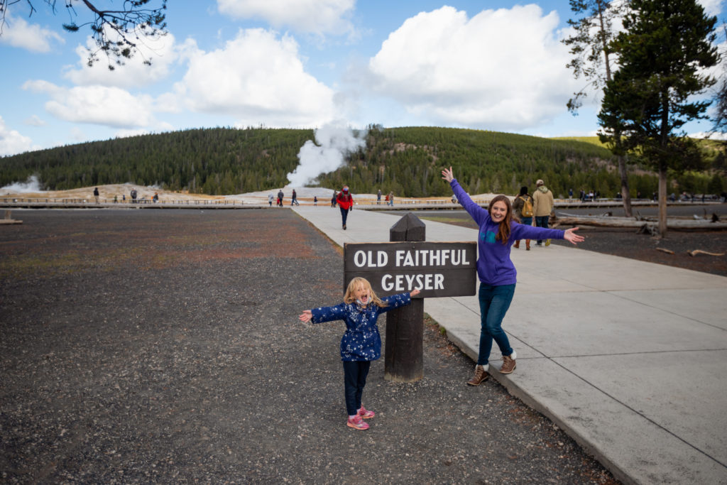 mom and daughter posing in front of Old Faithful in September