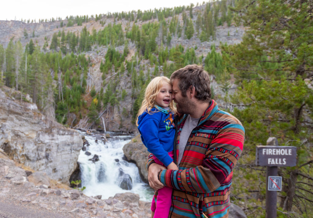 Dad and daughter in front of Firehole Falls in Yellowstone
